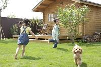 ログハウスの庭で遊ぶ男の子と女の子と犬