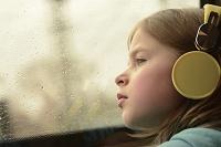 窓辺から遠くを見る少女