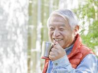 マグカップを持った笑顔のシニアの日本人男性