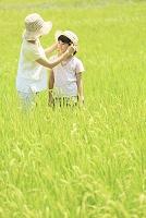 山梨県 娘の帽子に花飾りをする母親