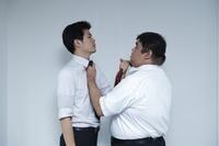 ネクタイを掴み合う日本人ビジネスマン
