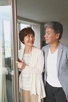 窓の側に立つ日本人のシニア夫婦
