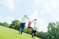 公園で娘の手を取って歩く両親の後ろ姿