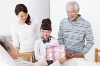 プレゼントを持つ孫と3世代家族