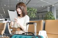 空港のラウンジでタブレットを触る日本人女性