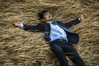 枯れ草に横たわる日本人ビジネスマン