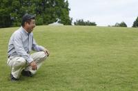 草原でしゃがむシニアの日本人男性