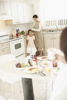 食卓のお父さんとママを手伝う女の子