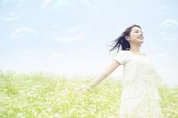 草原に立つ笑顔の日本人女性