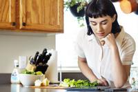 レシピを見ながら調理する若い女性