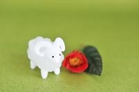 羊の置物と椿の花と和紙の背景