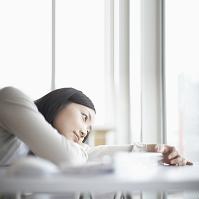 机に伏せる日本人女性