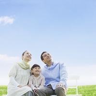 ベンチに座って見上げる日本人家族