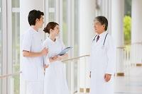 廊下で会話する看護師と医師