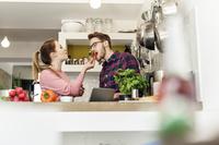 キッチンで料理する外国人カップル