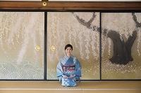 襖絵の前に正座する着物の日本人女性