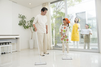 掃除をする中高年夫婦と孫男女