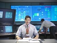 発電所の制御室で働く外国人男性