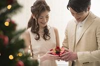 クリスマスツリー前でプレゼントを持つカップル