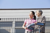バルコニーから眺めを楽しむ介護士さんとおばあちゃん