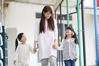 幼稚園の廊下を歩く保育士と園児