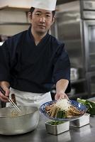 盛り付けた煮魚の皿を差し出す調理師