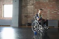 車椅子に乗りダンベルを使うシニアの男性