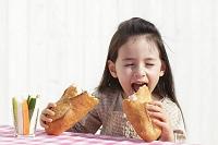 パンと野菜スティックを食べる女の子