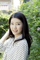 緑の中で微笑む20代日本人女性