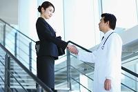 握手する医者とビジネスウーマン