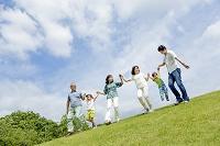 公園を手を繋いで歩く3世代