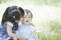ピクニックにて、日本人の赤ちゃんの面倒をみる女の子