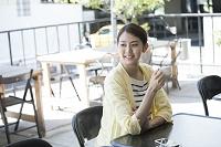 カフェテラスで微笑む20代日本人女性