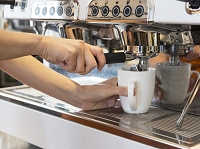 コーヒーを注ぐ女性の手元