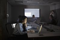 暗い会議室でラップトップを見る女性