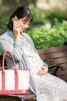 公園のベンチで電話をする妊婦の日本人女性