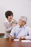 年賀状を書くシニアの日本人男性と女性