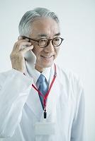 スマートフォンを使う白衣を着た70代男性