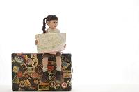 スーツケースに座り地図を見る女の子