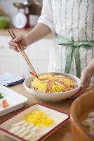 具材を盛り付けてちらし寿司を作る女性
