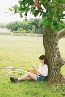新緑と本を読む日本人女性