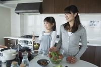 キッチンで料理をする女の子と母親