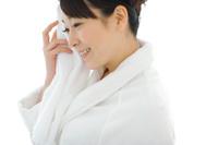 顔を拭いているバスローブを着た日本人女性