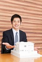 建築模型を差し出すビジネスマン