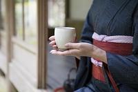 お茶を持つ着物の女性
