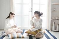 床に座って歯を磨く20代女性2人
