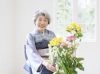 花を生ける着物のシニア日本人女性