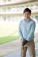 ゴルフクラブを持つ笑顔の日本人男性