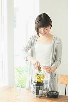 グリーンスムージーを作る若い日本人女性