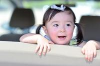 車の後部座席に座って笑っている日本人の女の子